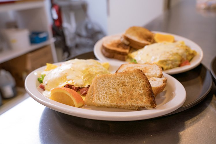 breakfast menu items at Raphael's that include an omlete toast and orange slices
